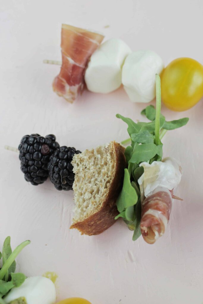 appetizer skewer with blackberries, french bread, arugula, and prosciutto .